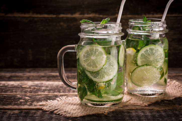 detox water with a lemon, lime and mint on a wooden table